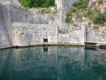 Reflection. Wall of Kotor Old City reflecting in water near fortress Stock Image