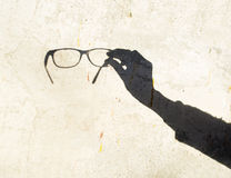 Reflection on wall: Spectacles in hand. The shadow from spectacles is on wall Stock Photo