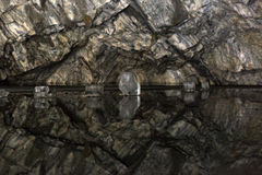 Reflection of the walls of the cave in a frozen underground lake. Stock Photo