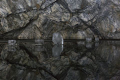 Reflection of the walls of the cave in a frozen underground lake. The marble quarry of Ruskeala in Karelia, an underground lake Stock Photo