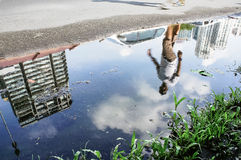 Reflection on water. Blur image of a guy walking on the street at city Royalty Free Stock Images