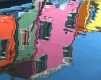 Reflection on the water of the colorful houses of the island. Of Burano in Italy stock photos