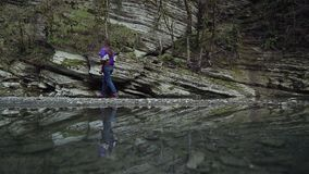 The reflection in the water of a girl who walks along a stone cliff. FullHD stock video