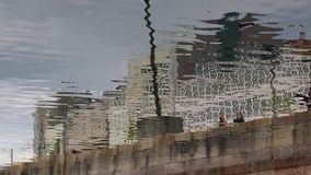 Reflection in the water of people walking stock video footage