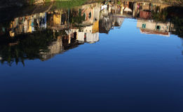 Reflection in the water of a pond, houses in the v Royalty Free Stock Photography