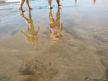 Reflection on the water of the sand of a beach of a tropical seashore during a low tide showing the feet of several persons. Walking and the reflection of their stock photography