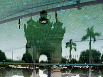 Patuxai reflected on water surface. An up side down reflection of Patuxai and palm trees on a water surface Stock Images