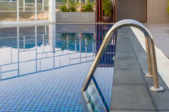 Reflection of water,Swimming pool with steel ladderbar. Royalty Free Stock Image