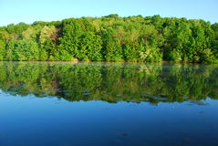 Reflection. Water reflection of trees and sky across smooth water royalty free stock photos