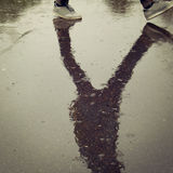 Reflection in the wet asphalt. Walking teenager. Stock Photography
