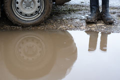 Reflection wheel car in a muddy puddle and men's shoes Stock Photos