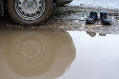 Reflection wheel car in a muddy puddle and men's shoes Royalty Free Stock Photography
