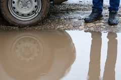 Reflection wheel car in a muddy puddle and men's shoes Royalty Free Stock Images