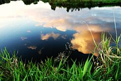 Reflection of White Clouds on Pond Royalty Free Stock Images