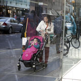Reflection in the window. A woman is pushing a red stroller with a sleeping baby. People walk at Covent Garden. Stock Image