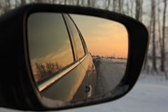 Reflection winter road in the mirror of car at Royalty Free Stock Photo