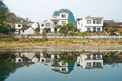 Reflection of a winter village. Reflection of village houses on calm water royalty free stock photo