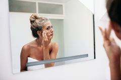 Reflection of a woman applying cosmetic cream Stock Photo
