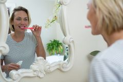 Reflection of woman brushing her teeth royalty free stock photos