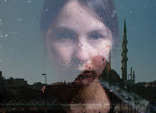 Reflection of woman and mosque in the window Royalty Free Stock Photo