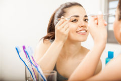Reflection of a woman plucking her eyebrows. Portrait of a young Hispanic woman looking at a mirror in the bathroom while plucking her eyebrows with tweezers stock photography