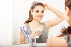 Reflection of a woman putting on deodorant. Attractive Hispanic young woman putting on deodorant while looking at herself in a mirror in the bathroom royalty free stock images