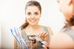 Reflection of a woman putting on makeup. Closeup of a pretty young brunette applying some makeup on her eyes in front of a bathroom mirror Royalty Free Stock Photography