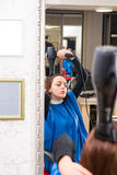 Reflection of Woman in Salon Blow Drying Hair Royalty Free Stock Image