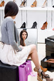 Reflection of woman trying on high heeled shoes. Reflection of woman sitting on chair and trying on new high heeled shoes in the shop Royalty Free Stock Photography