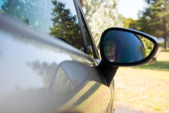 Reflection of woman in wing mirror driving a car Stock Photography