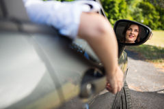 Reflection of woman in wing mirror driving a car Stock Photos