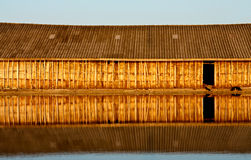 Reflection of wood house in water Stock Images