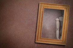 Reflection of wooden dummy in framed mirror. Hanging on textured wall.Illustration stock photo