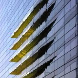 Reflection of a yellow building reflected in glass Royalty Free Stock Photography