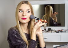 Reflection of young beautiful woman applying her make-up Royalty Free Stock Image