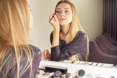 Reflection of young beautiful woman applying her make-up Stock Photography