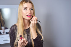 Reflection of young beautiful woman applying her make-up Stock Image