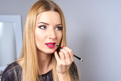 Reflection of young beautiful woman applying her make-up Stock Photos