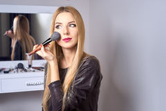 Reflection of young beautiful woman applying her make-up Royalty Free Stock Photos