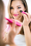 Reflection of young beautiful woman applying her make-up Royalty Free Stock Photography