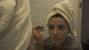 Reflection of young beautiful woman with towel on head applying her make-up mascara after taking a shower, looking in a stock footage