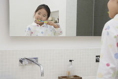 Reflection Of Young Girl Brushing Teeth Royalty Free Stock Images