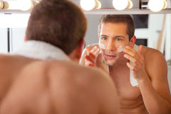 Reflection of young man in mirror applying shaving cream Stock Images