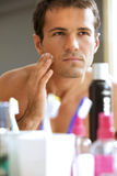 Reflection of young man in mirror applying shaving cream Royalty Free Stock Photo
