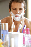 Reflection of young man in mirror applying shaving cream Royalty Free Stock Photography