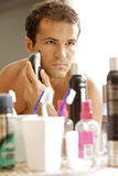 Reflection of young man in mirror shaving with electric shaver Stock Images