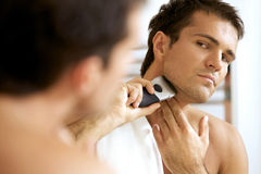 Reflection of young man in mirror shaving with electric shaver Royalty Free Stock Images