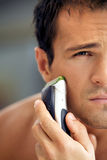 Reflection of young man in mirror shaving with electric shaver Royalty Free Stock Photography