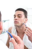 Reflection of young man shaving in bathroom mirror Royalty Free Stock Images