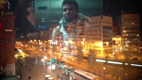 Reflection of young men using glass elevator at shopping mall, night city life. Stock footage stock footage